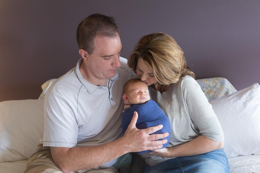 parents snuggling newborn baby boy
