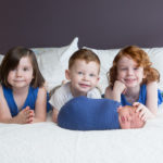 three older siblings with newborn brother