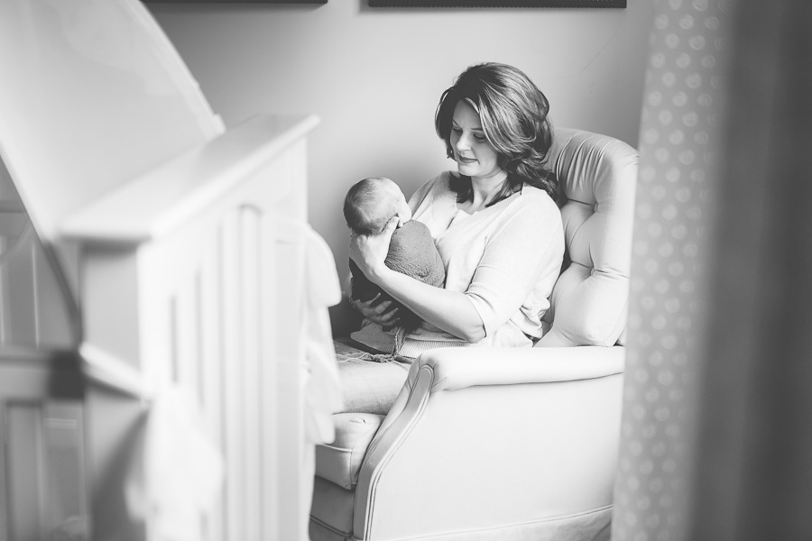 new mother holding newborn son black and white