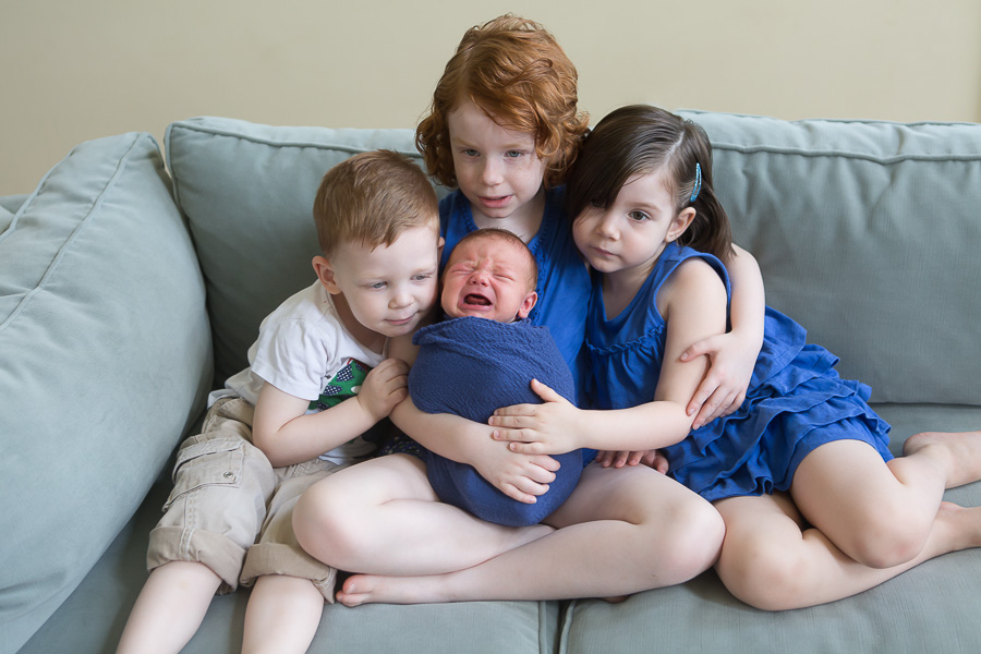 older brother and sisters comforting crying newborn baby