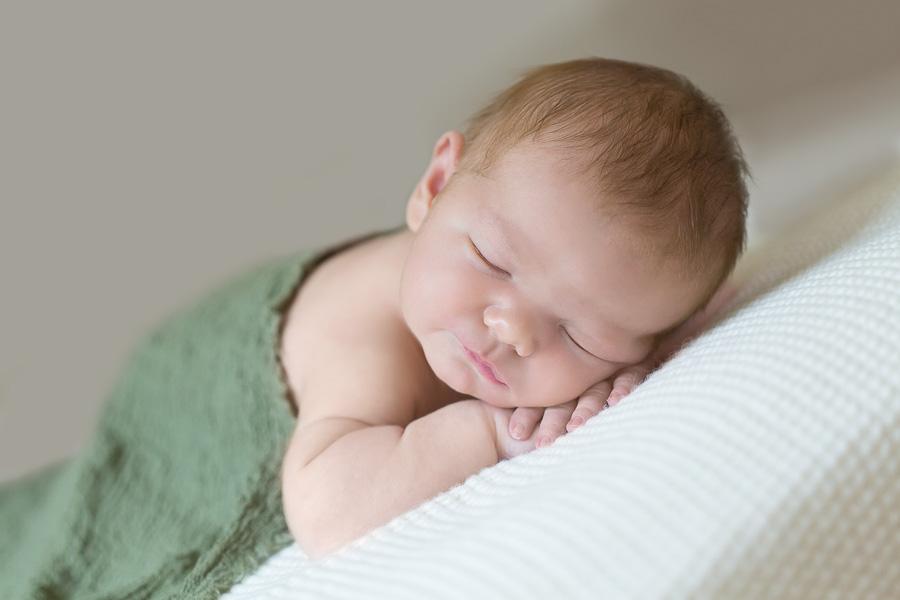 6 day old baby boy sleeping under green blanket