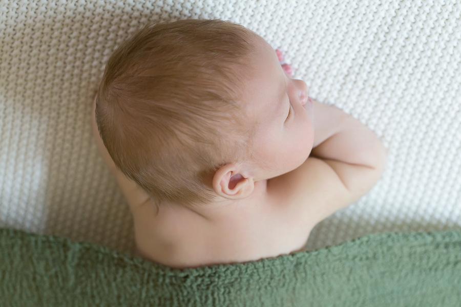 newborn boy sleeping on hands under green blanket